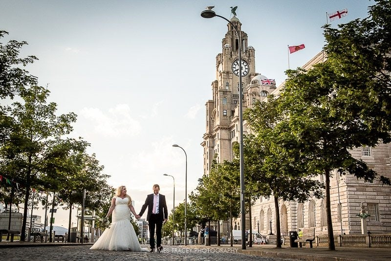 bride and groom walking by liver building