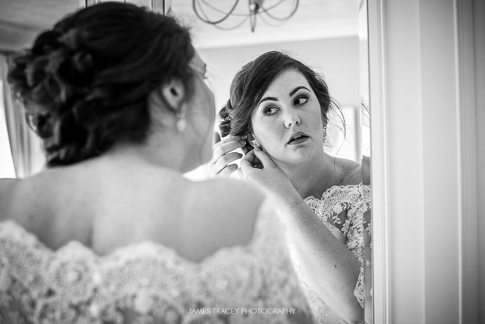 bride putting ear rings on