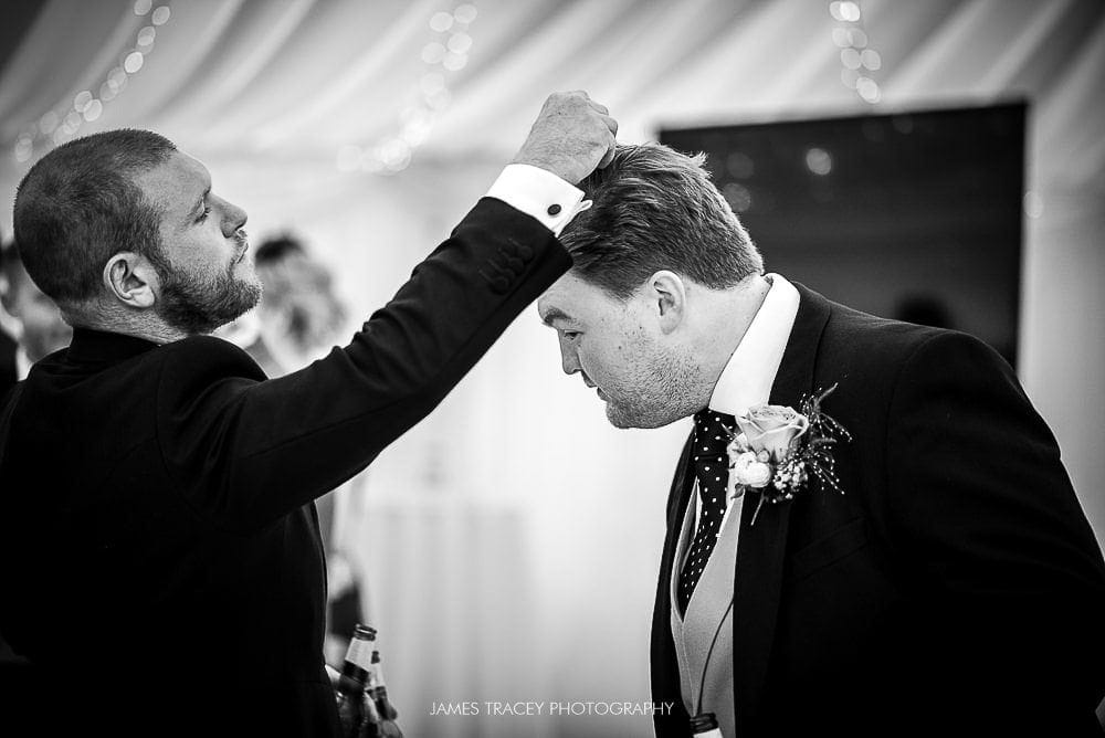 groom having confetti removed from his hair