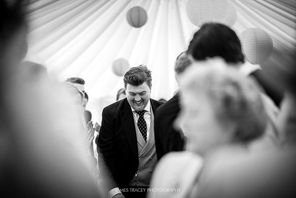 groom walking into reception