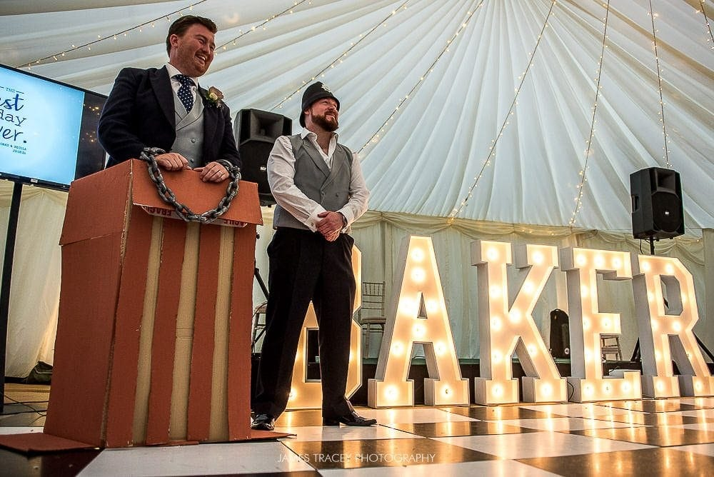 groom in the dock in front of light up letters