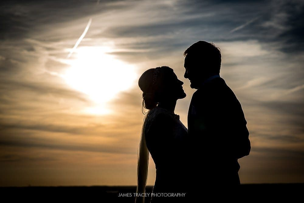bride and groom in front of sunset