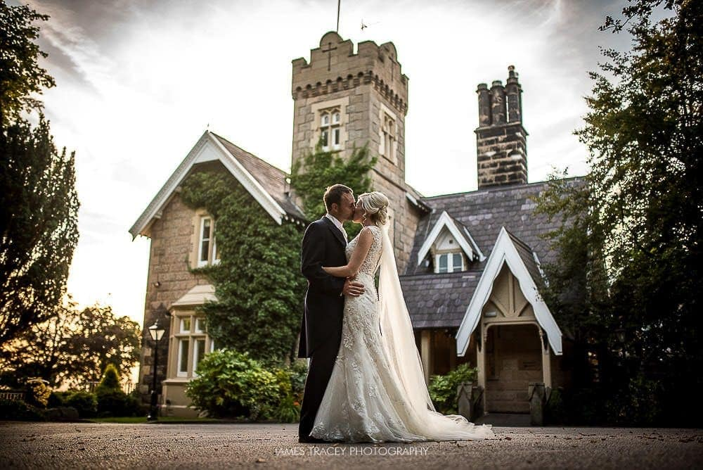 bride and groom kissing in front of west tower