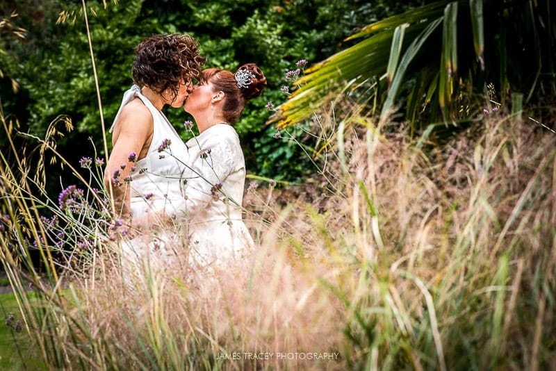 brides kissing in a park
