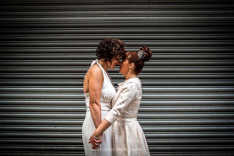 brides kissing in front of a shutter