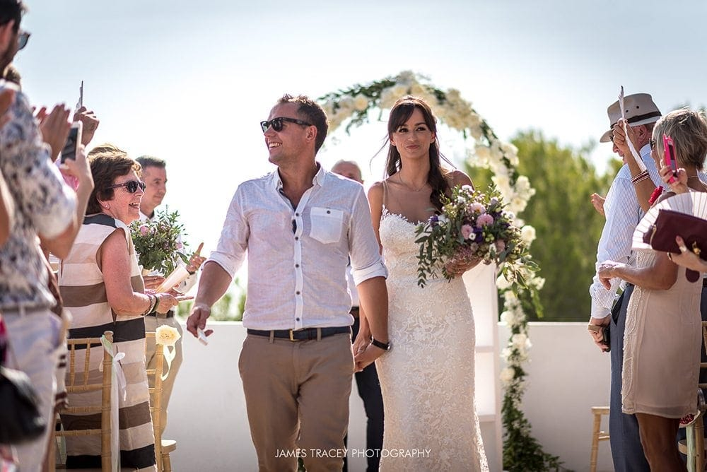 bride and groom walking back down the aisle in ibiza
