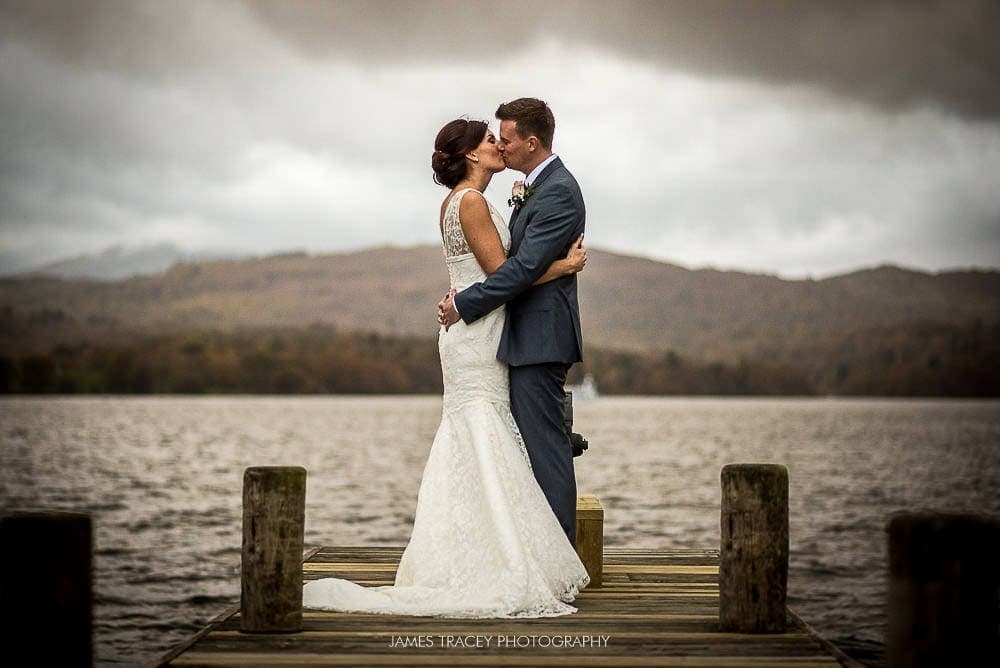 bride and groom kissing on lake windermere