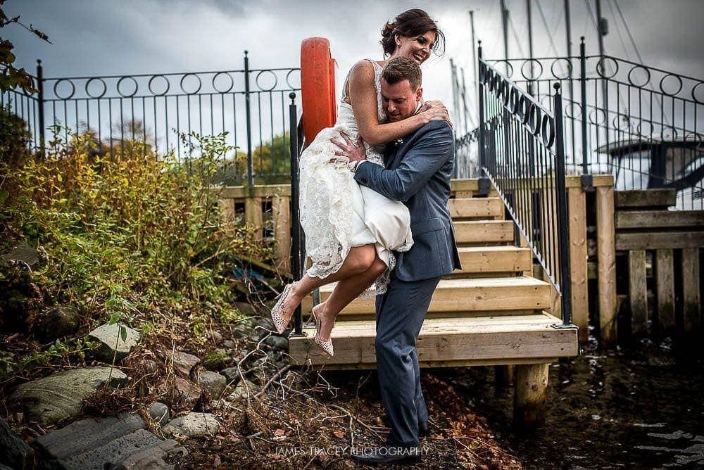 groom helping bride jump down stairs