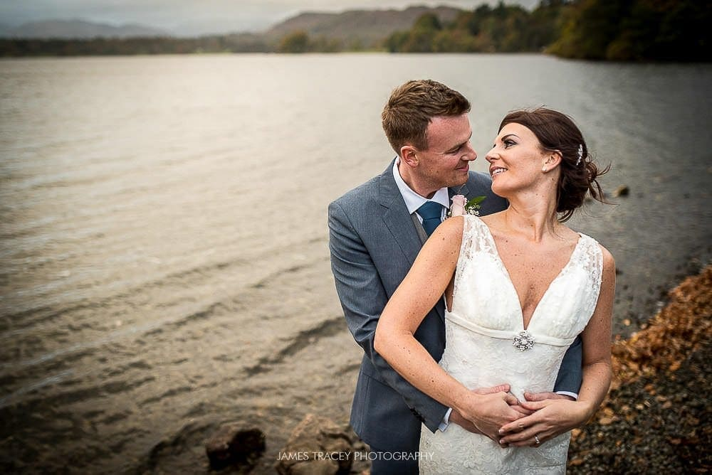 bride and groom in front of lake windermere