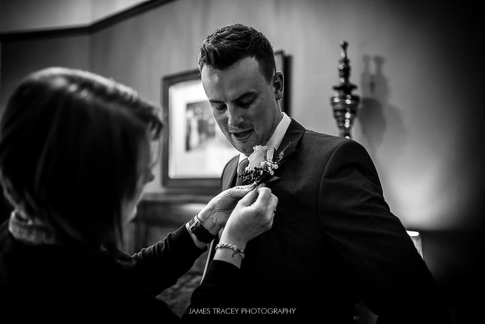 groom having flower pinned on