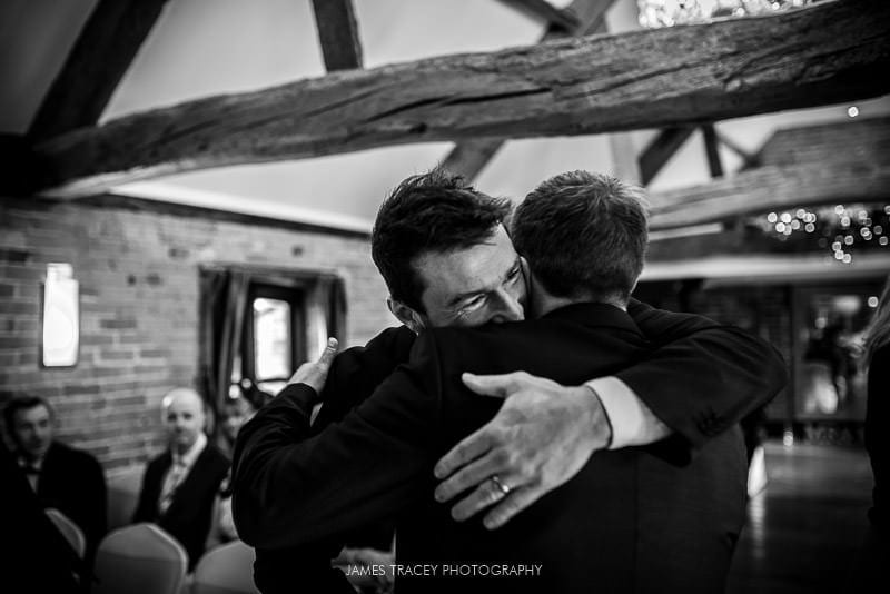 groom gettinng hugged at wedding at swancar farm