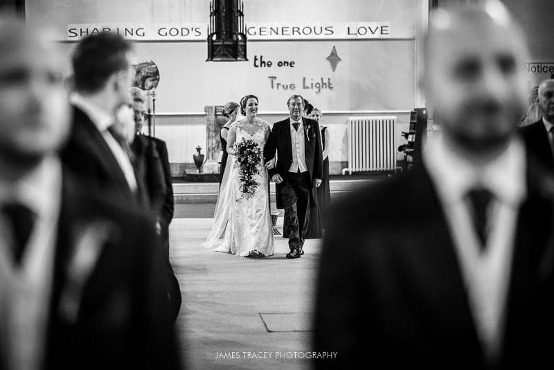 bride and her father walking up the wedding aisle