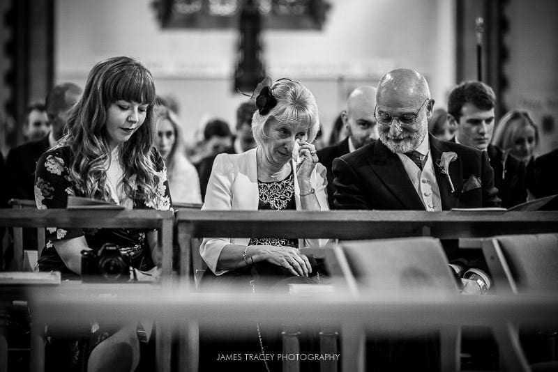 wedding guest wiping tears from her eyes