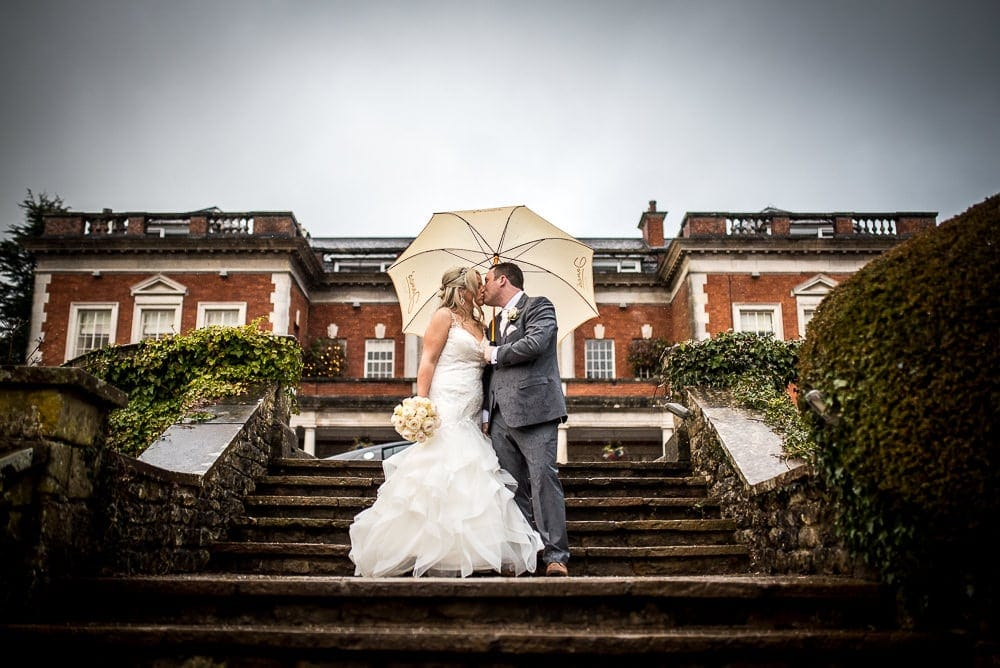 bride and groom kissing on steps at eaves hall