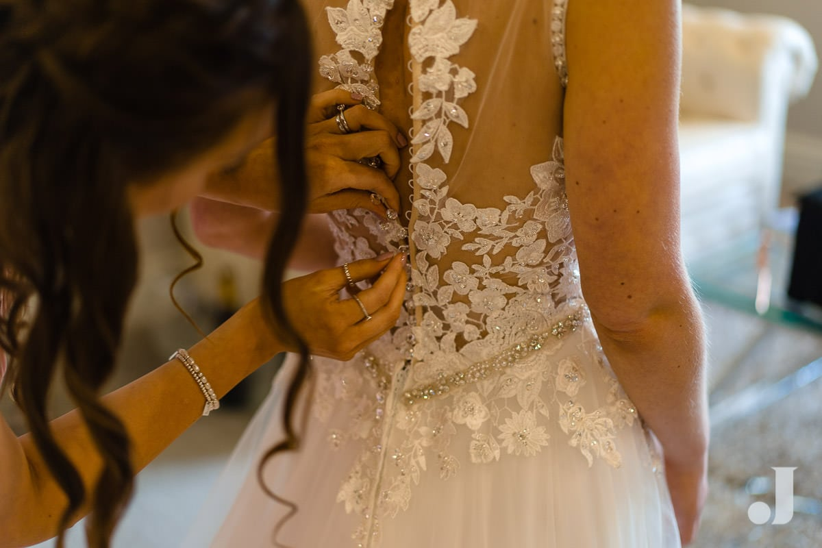 brid ebeing buttoned into wedding dress at merrydale manor