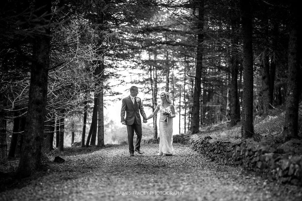 bride and groom walking in woods