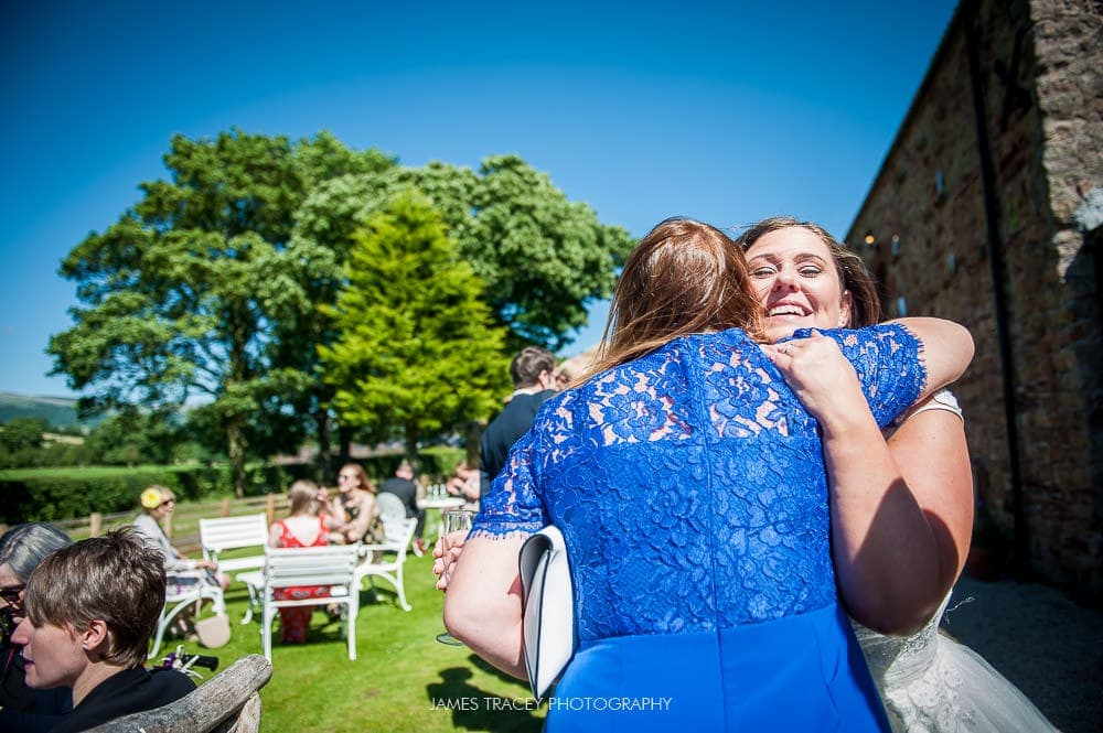 guest hugging bride at eden wedding barn