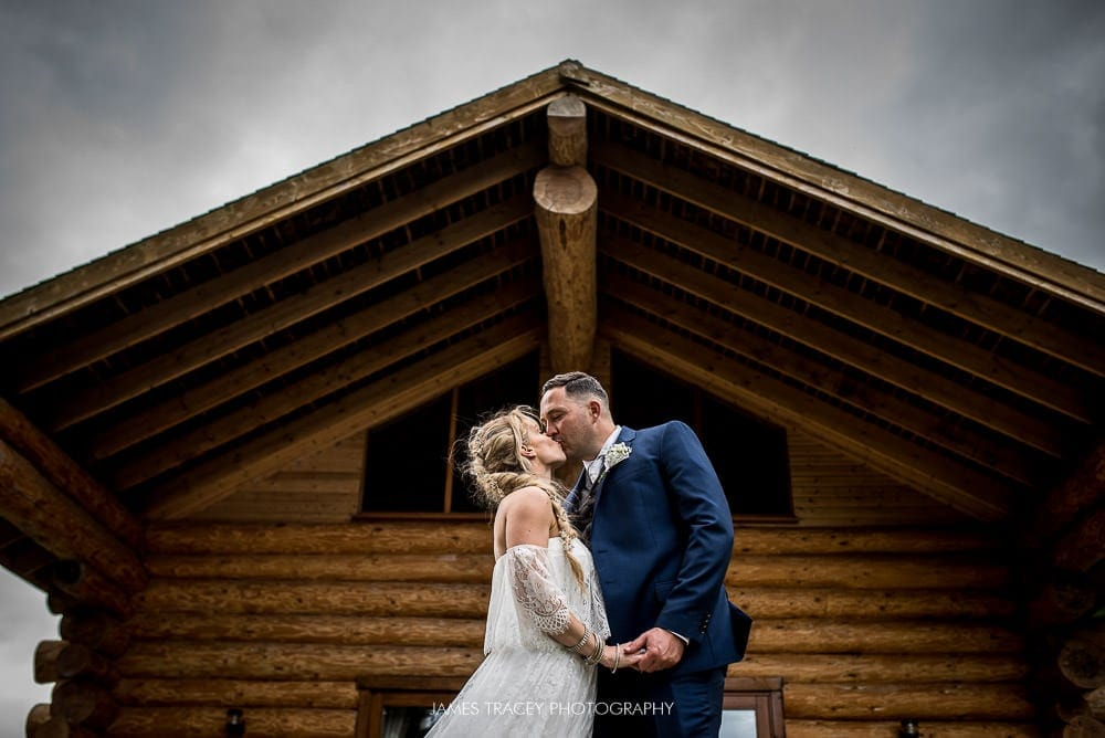 bride and groom kissing at hidden river cabin
