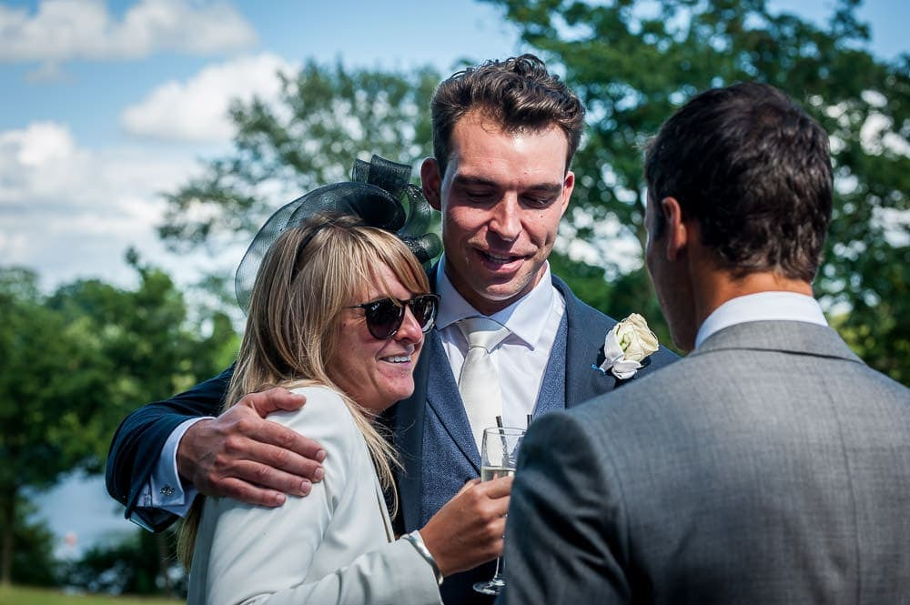 groom hugging a wedding guest