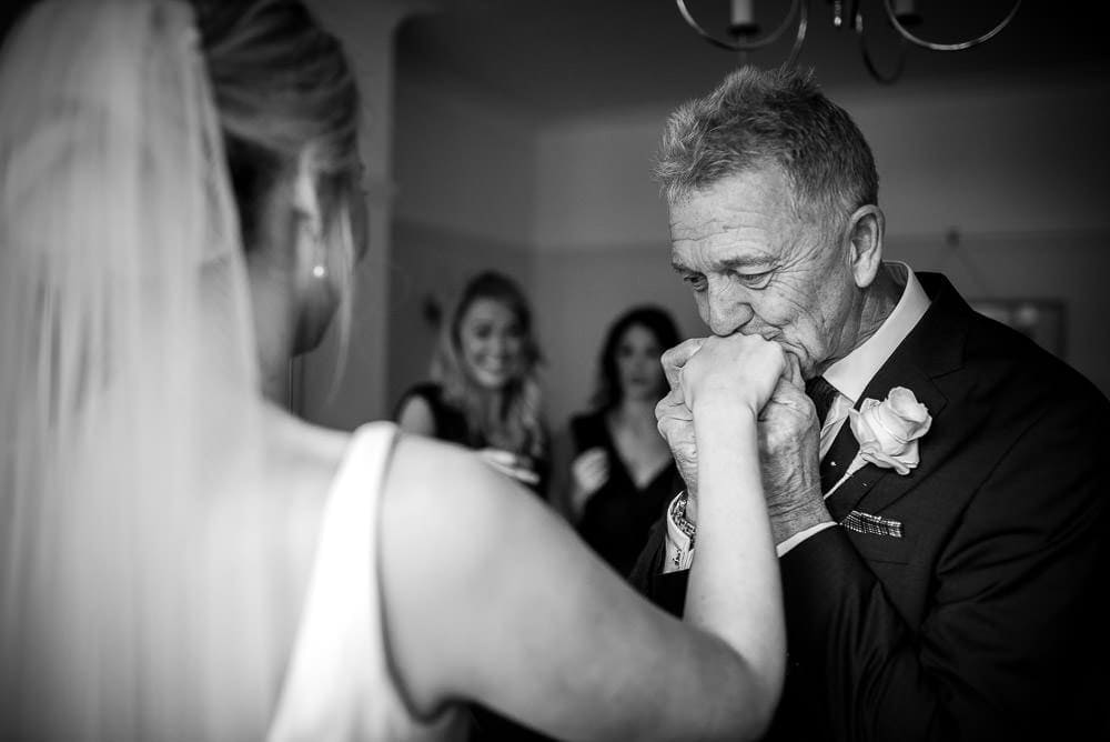 fathre of the bride kissing his daughters hand