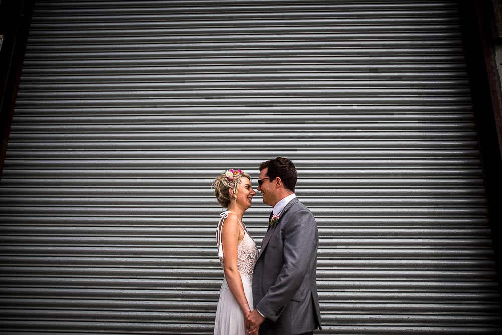 bride and groom in front of shutters