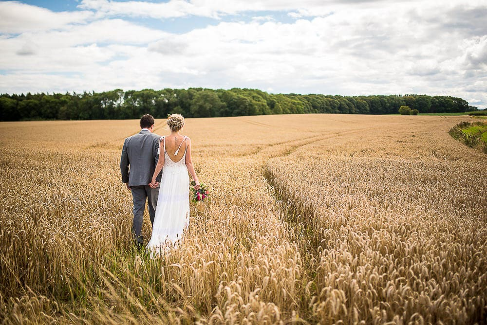 bride and groom walking in corn fields at priory cottages