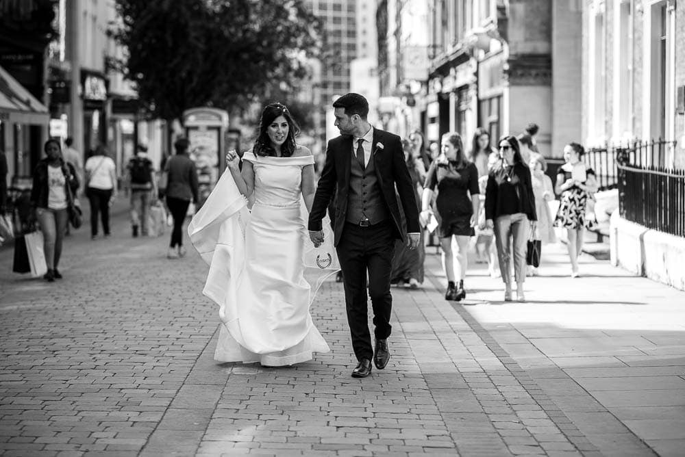 bride and groom walking through the streets of manchester