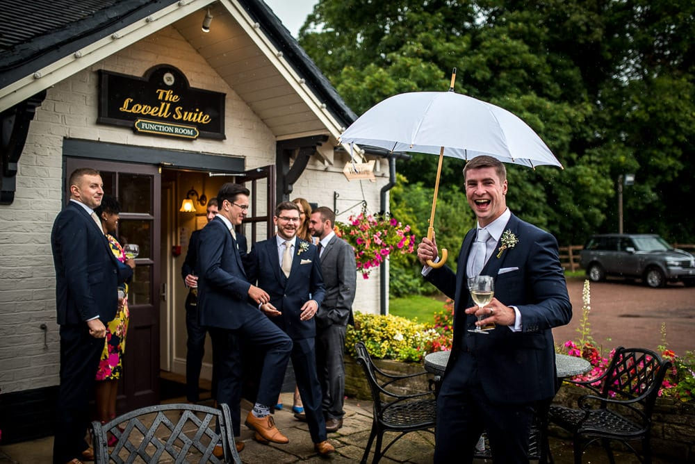 groom with umbrella at swettenham arms