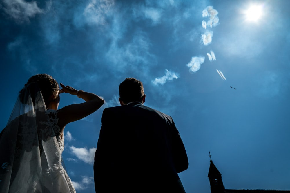 bride and groom watching acrobatic display over Peckforton Castle Wedding