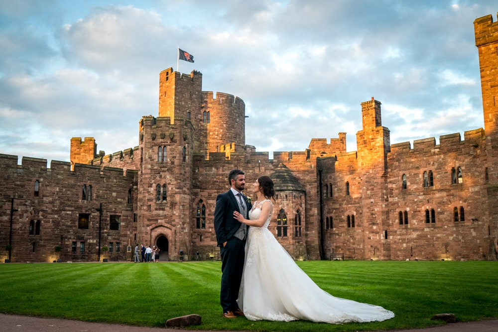 Bride and groom in front of Peckforton Castle at sunset