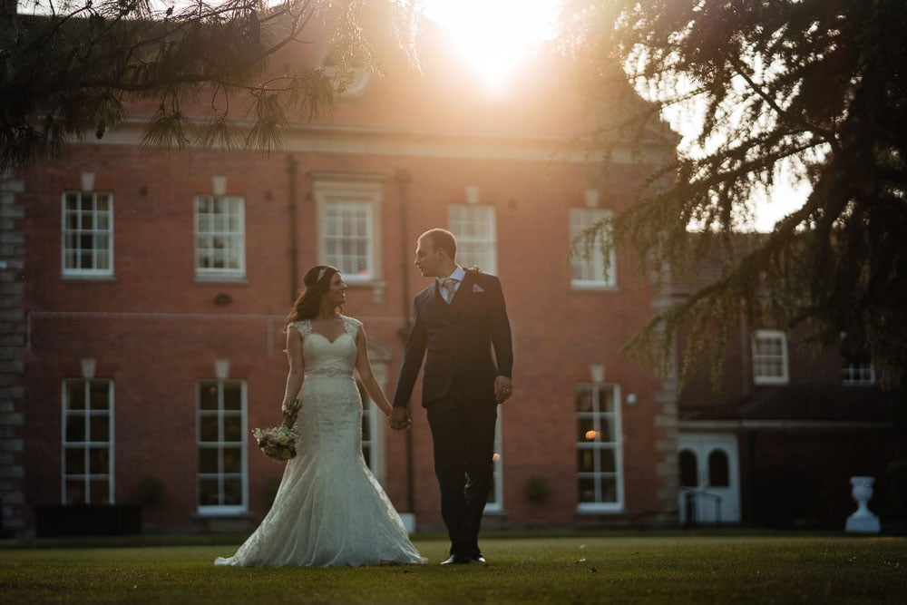 bride and groom walking at sunset at mottram hall