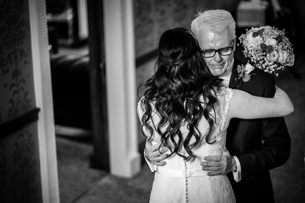 emotional father of the bride hugging daughter