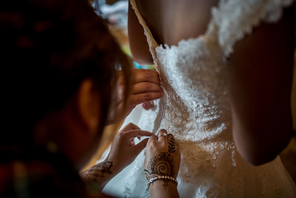 bride having her wedding dress buttined up