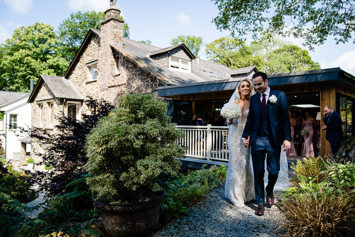 bride and groom leading guests through gilpin lake house gardens