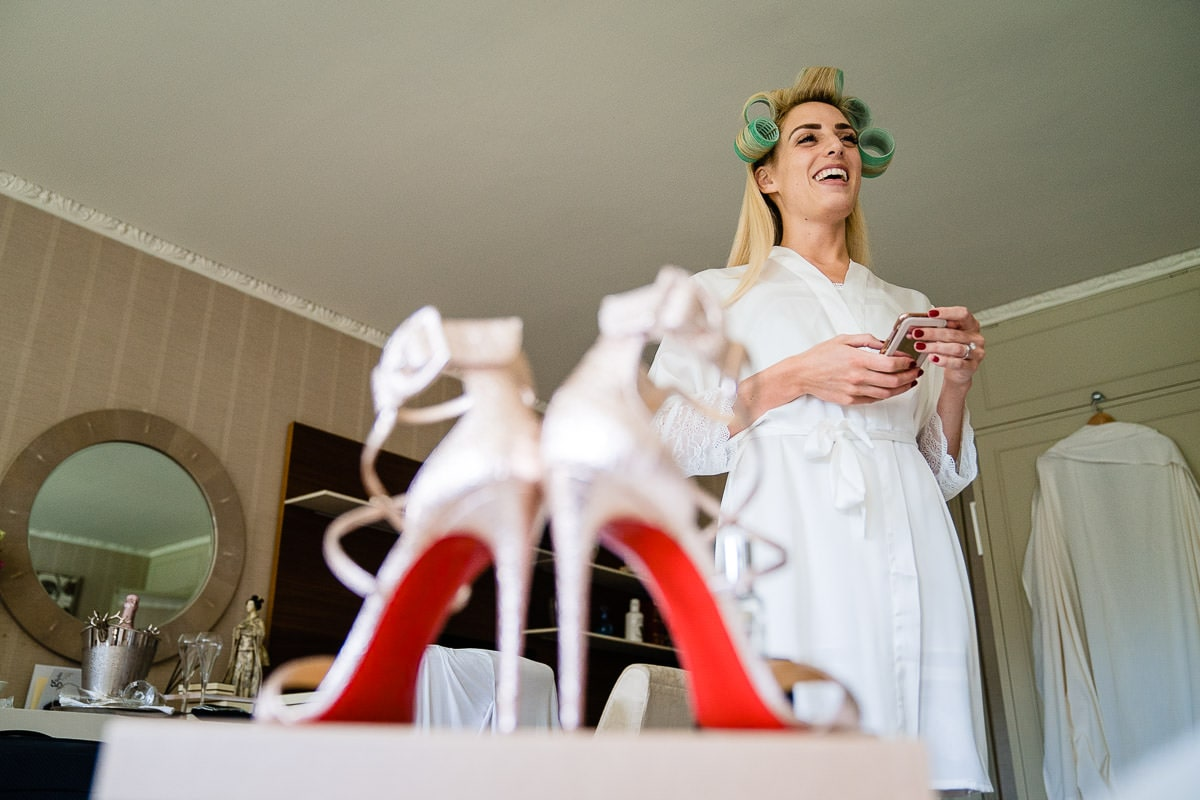 bride laughing in front of louboutins