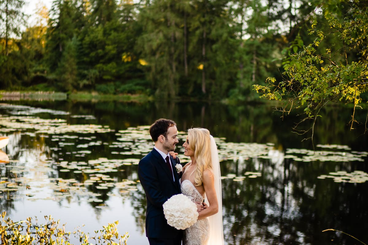 bride and groom in front of lake at gilpin lake house