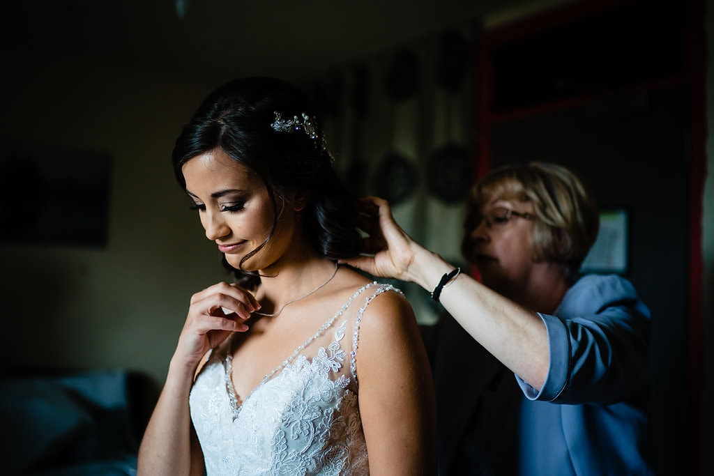 emotional bride looking at sentimental necklace on her wedding day