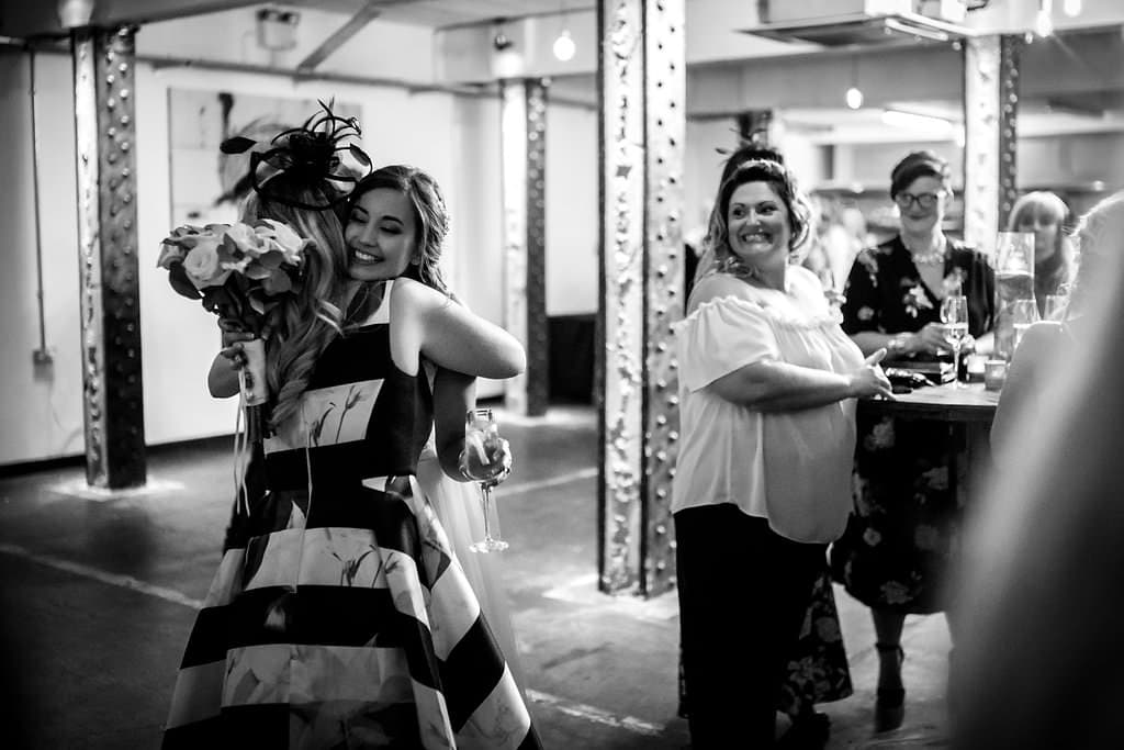 guests hugging couple at victoria warehouse wedding