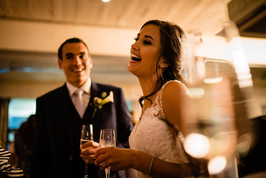 bride laughing in front of her new husband