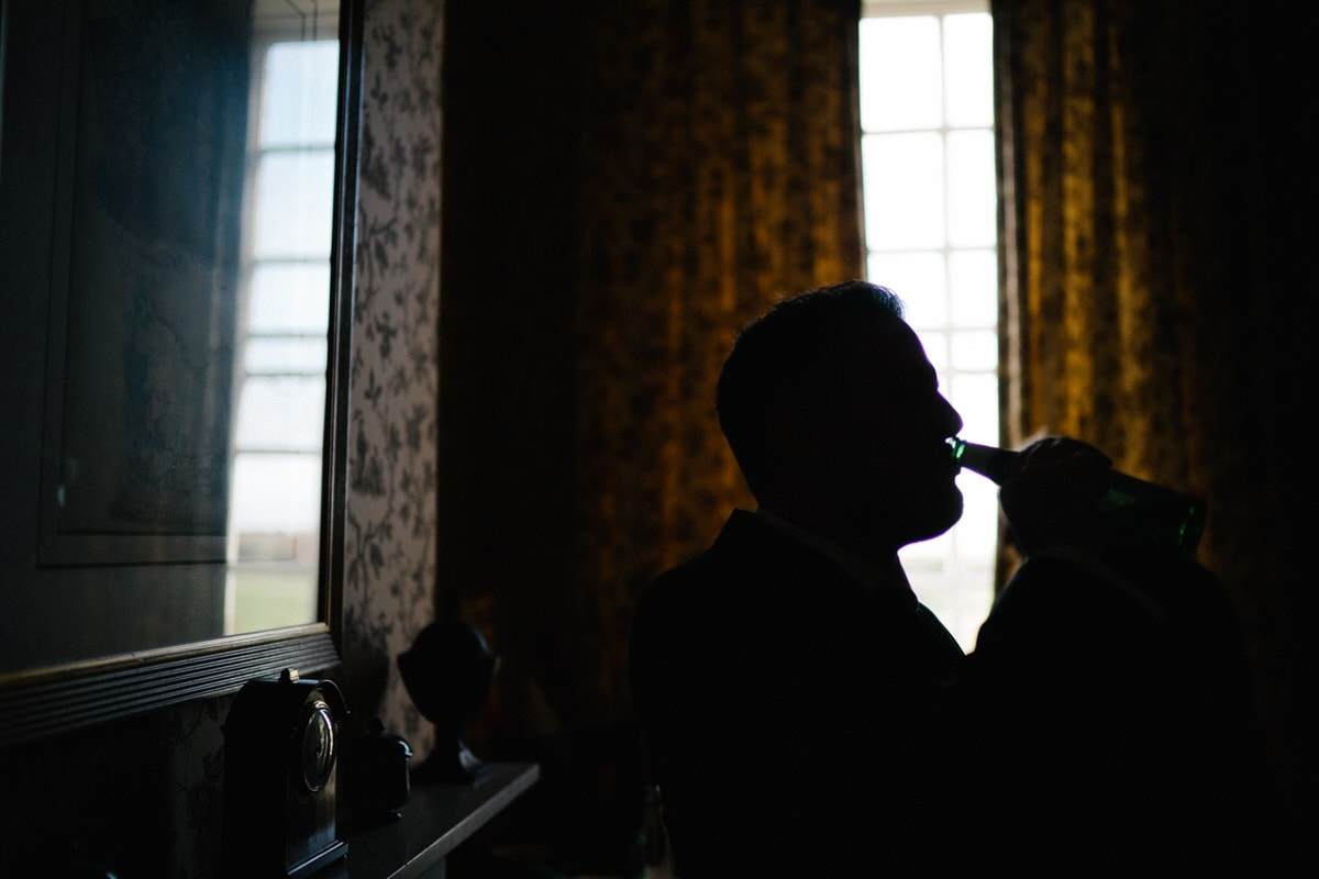groom having a beer at his wedding