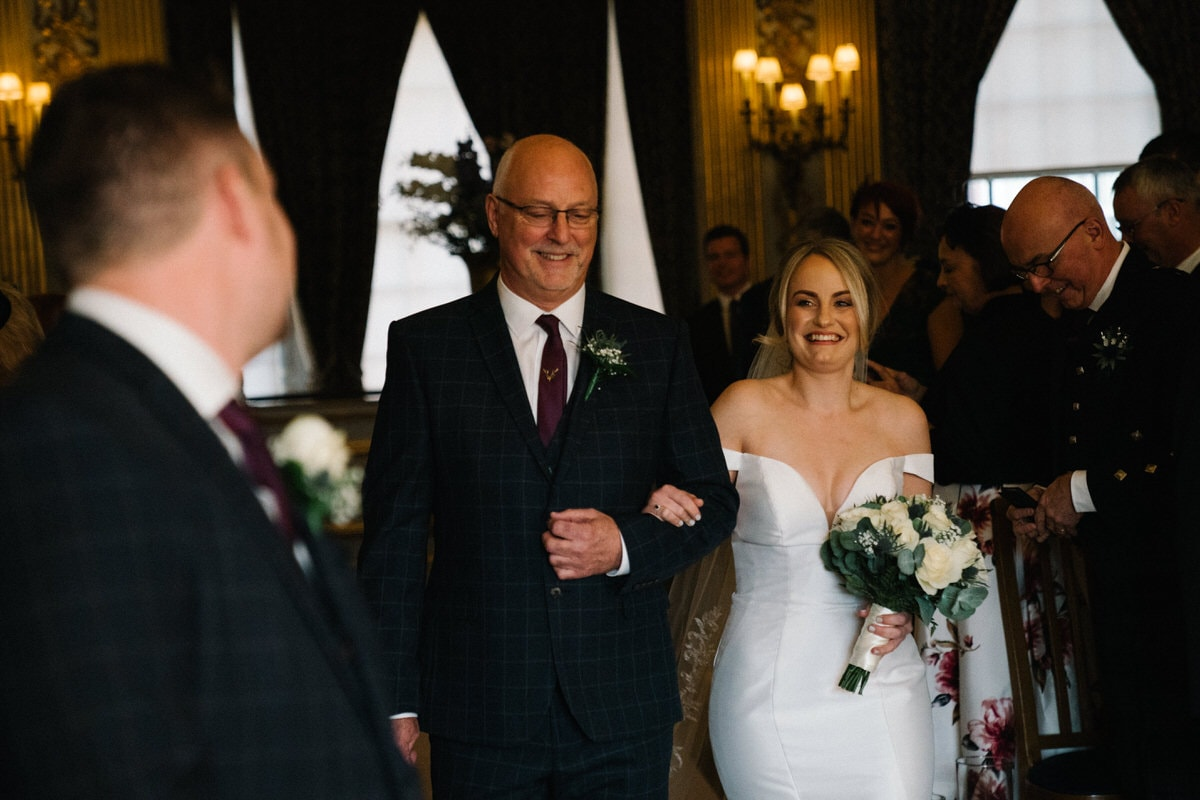 bride walking up the aisle at knowsley hall wedding