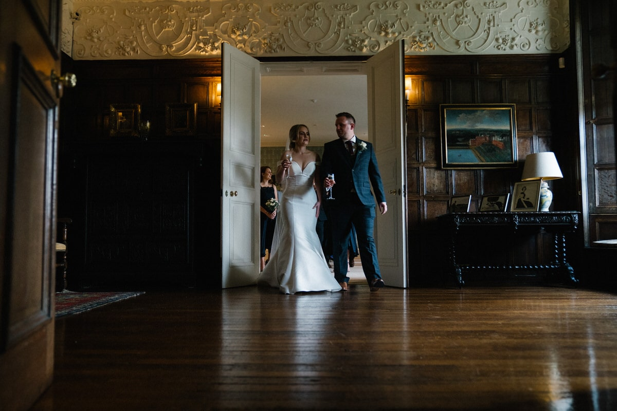 bride and groom leading their guests through knowsley hall
