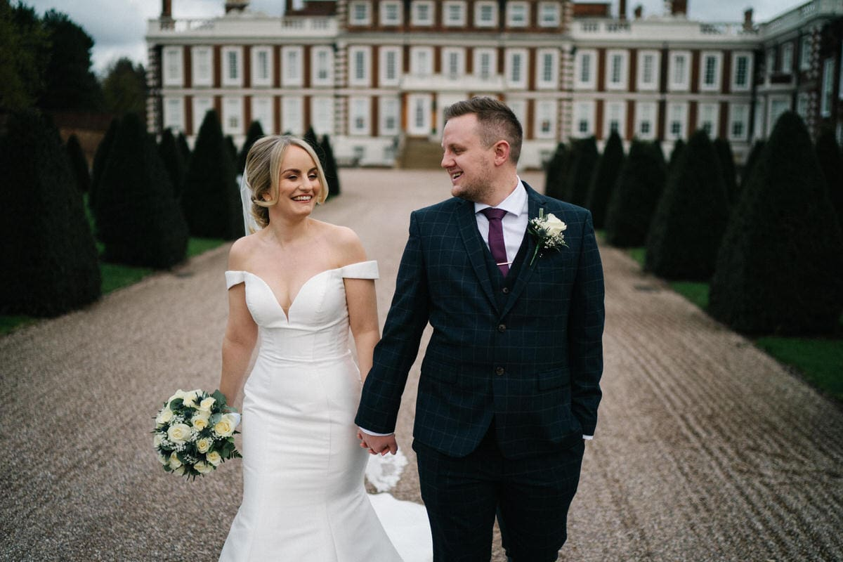 bride and groom walking on path at front of knowsley hall