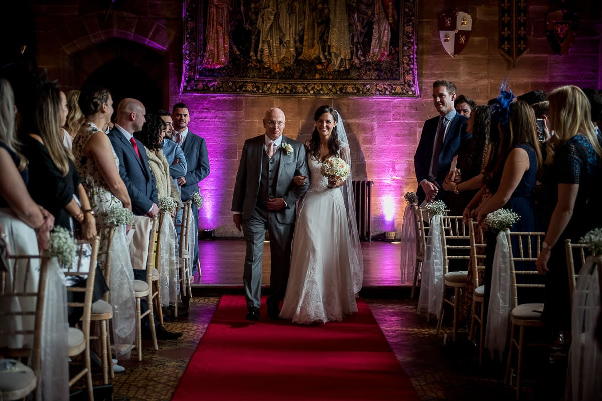 bride walking up the aisle at peckforton castle wedding
