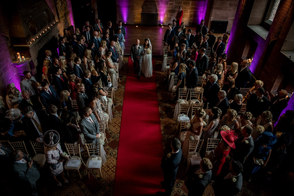 dramatic photo of bride walking up the ailse at peckforton castle wedding