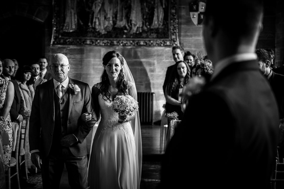 black and white photo of bride walking up the aisle at peckforton castle