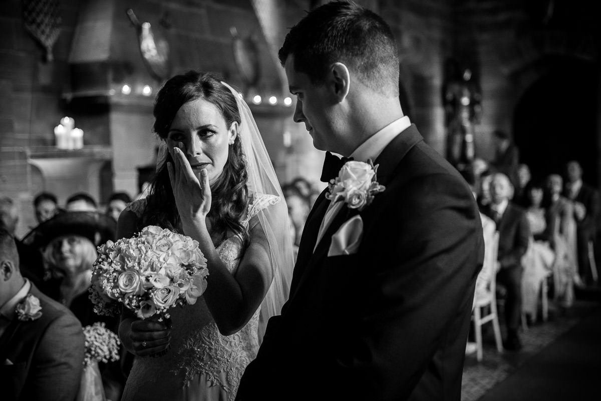 bride wiping tear from her eye at peckforton castle