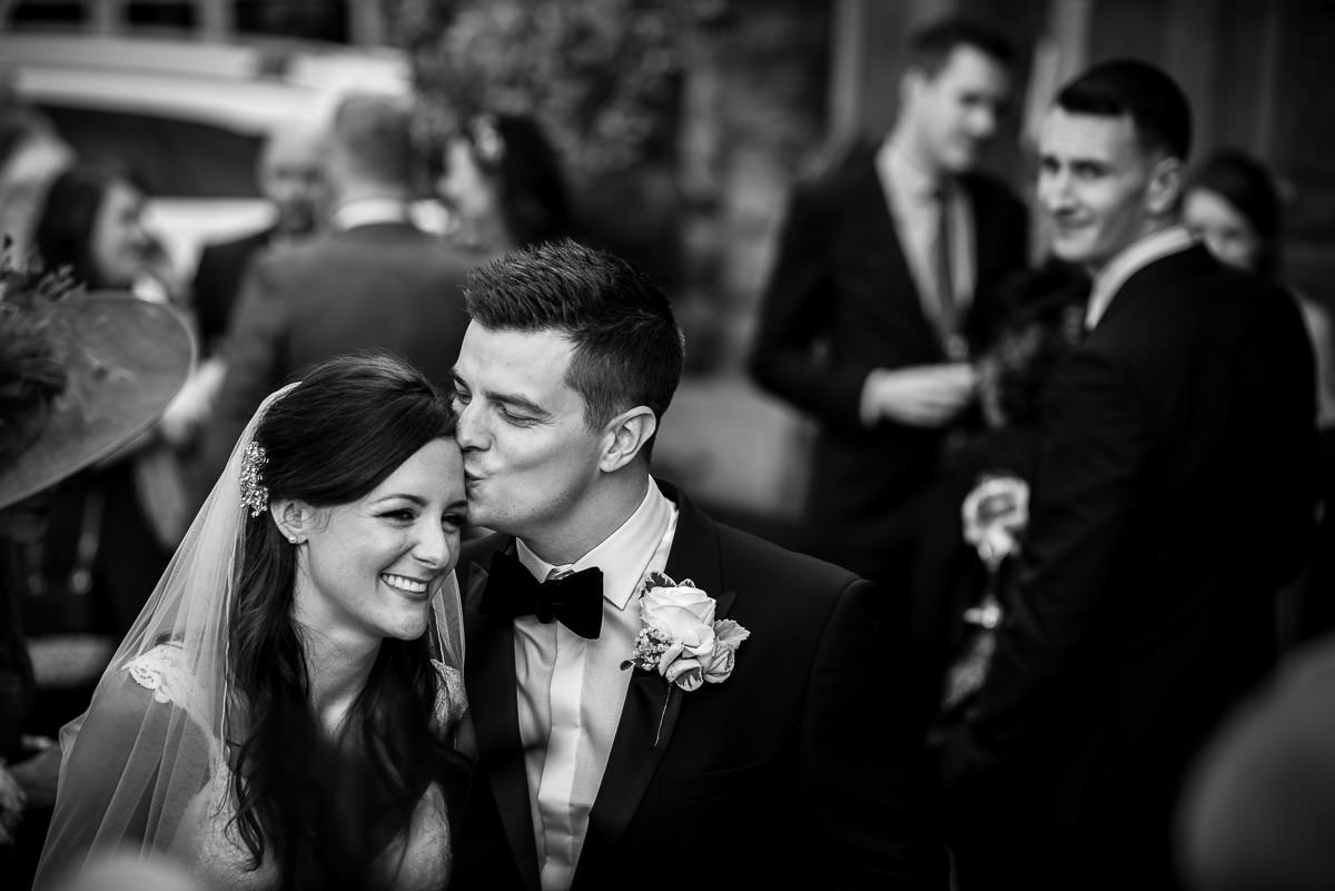 groom kissing bride at their peckforton castle wedding