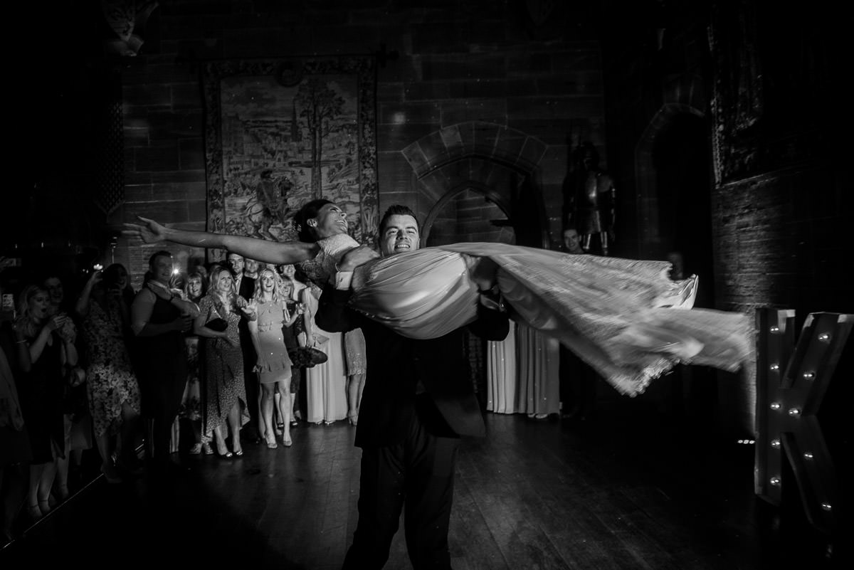 groom lifting bride during their peckforton castle first dance