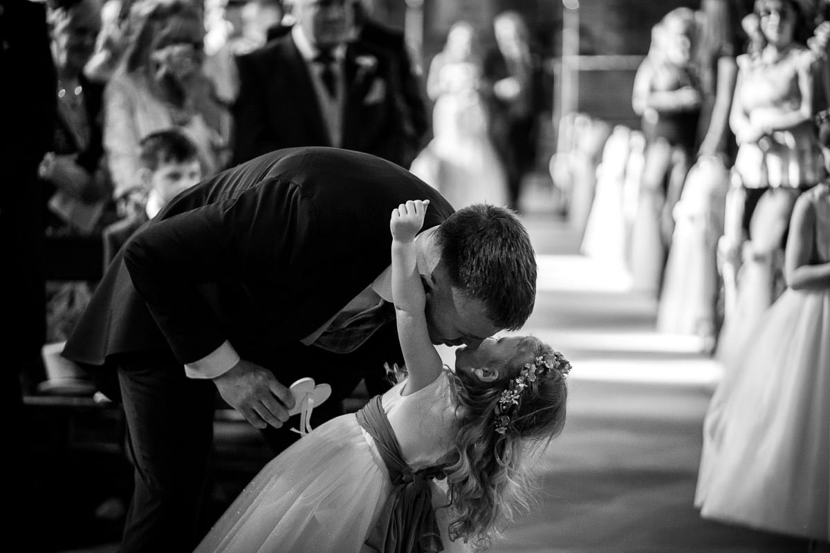 groom kissing his daughter at wedding
